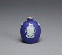 Small snuff bottle of white jasper with dark blue jasper dip and white relief decoration with on one side the arms of the City of Hanley (UK) and the name HANLEY in a banner below, on either side a goat's head mask.