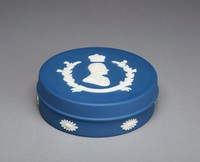 """Round covered box of solid royal blue jasper with white relief decoration, around the sides of the body are small floral motifs and on the cover is the portrait bust of Prince Philip, Duke of Edinburgh in civil dress beneath a crown with two laurel branches with berries and a banner below that reads, """"HRH DUKE OF EDINBURGH."""""""