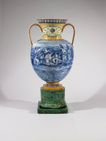"""Large vase of creamware and jasperware constructed of seven pieces (plinth, base, foot, body, two handles, neck), the fluted base and square plinth are of blue, white, brown, and beige jasper combined to create a marbled effect, then covered with a lead glaze to resemble green malachite; the yellow foot has a central blue and white band decorated with a wavescroll pattern; the two loop handles are decorated with yellow bands down each side, the central handle has a white ground on both sides decorated with stylized green and yellow leaf-and-berry vines; the neck is likewise yellow highlighted with a repeating star pattern, on either side is a central reserve of a lighter yellow color and outlined with blue foliate motifs, in the middle of each in blue is a tripod urn above two crossed leafy branches, the lip with a blue egg-and-dart pattern; the central ovoid body depicts in monochrome blue the scene of Alexander the Great, accompanied by his friend Hephaestion, entering the tent of the Persian king Darius III after """"La tente de Darius"""" by Charles Le Brun (1619-90) from the """"Triumphs of Alexander"""" series painted between 1662 and 1673 (now in the Louvre). Lessore used as a prototype an engraving by Gérard Edelinck (Flemish, 1640-1707), which was made to complete the series otherwise engraved by Gérald Audran (French, 1640-1703). The painting, which continues around the body of the vase shows on the reverse a landscape typical of Northern Africa."""