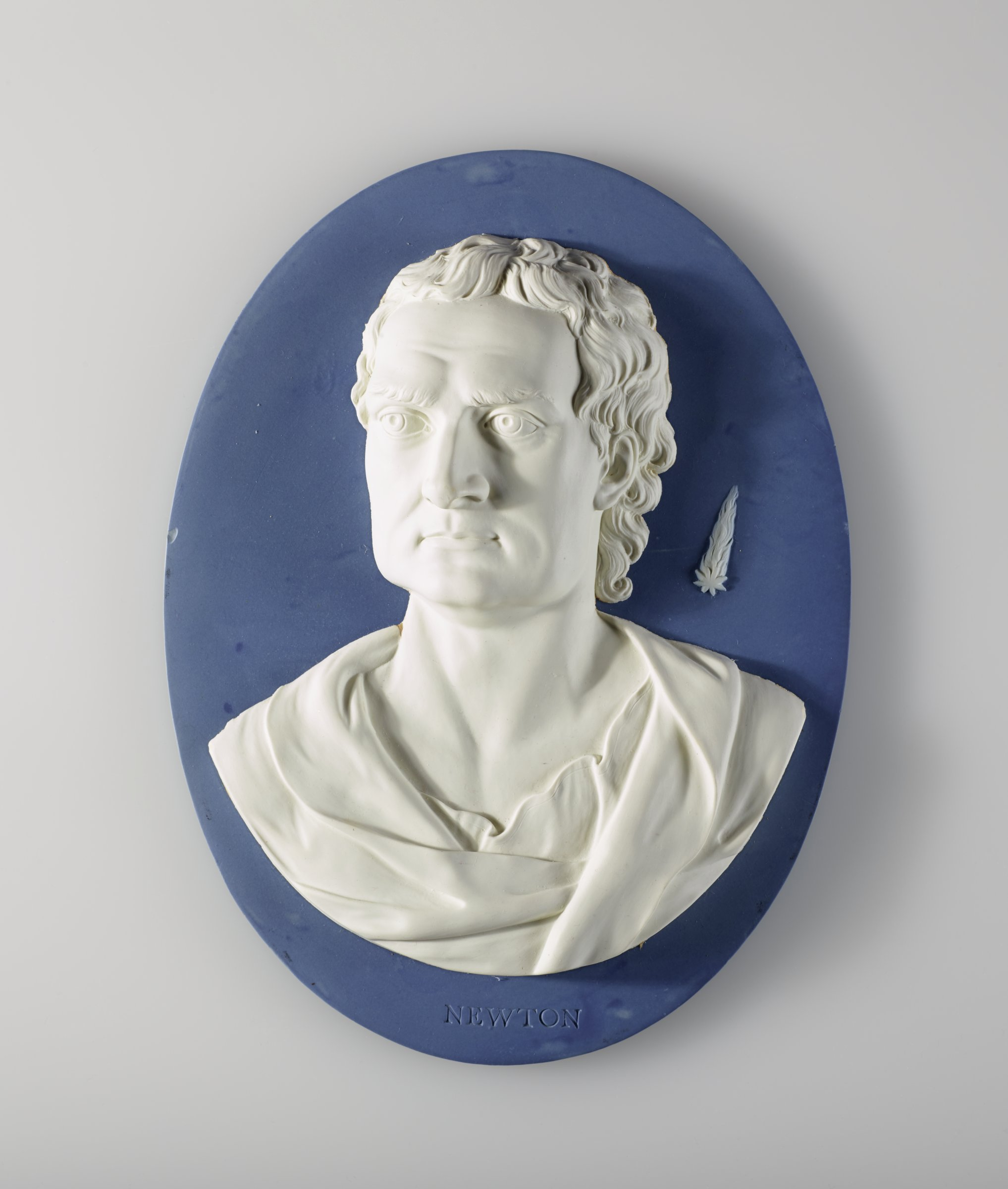 Large, heavy oval portrait medallion of light blue jasper with blue jasper dip and white relief, with the portrait of Sir Isaac Newton (1643-1727), English mathematician, astronomer and physicist, in classical drapery facing almost front, behind him in white relief Newton's comet of 1680, the first comet discovered by telescope.