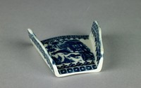 """Small asparagus shell of white soft-paste porcelain with low vertical, scalloped sides that taper towards one end, open at both ends to allow bundles of asparagus spears to be contained inside, the interior printed sideways in underglaze blue in the """"Fisherman"""" or """"Pleasure Boat"""" pattern, above and below the printed scene and on the interior and exterior sides a border of small blue square elements with a white dot in the middle above a repeating C-scroll and dot pattern."""