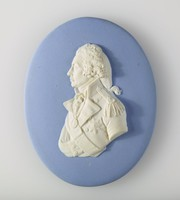 Oval blue jasper medallion with white relief profile portrait of Admiral Horatio Nelson (1758-1805) shown with the sash and star of the Knight of the bath, was a British flag officer in the Royal Navy. He was noted for his inspirational leadership, superb grasp of strategy, and unconventional tactics, which together resulted in a number of decisive naval victories, particularly during the Napoleonic Wars. He was wounded several times in combat, losing the sight in one eye in Corsica and most of one arm in the unsuccessful attempt to conquer Santa Cruz de Tenerife. He was shot and killed during his final victory at the Battle of Trafalgar in 1805.