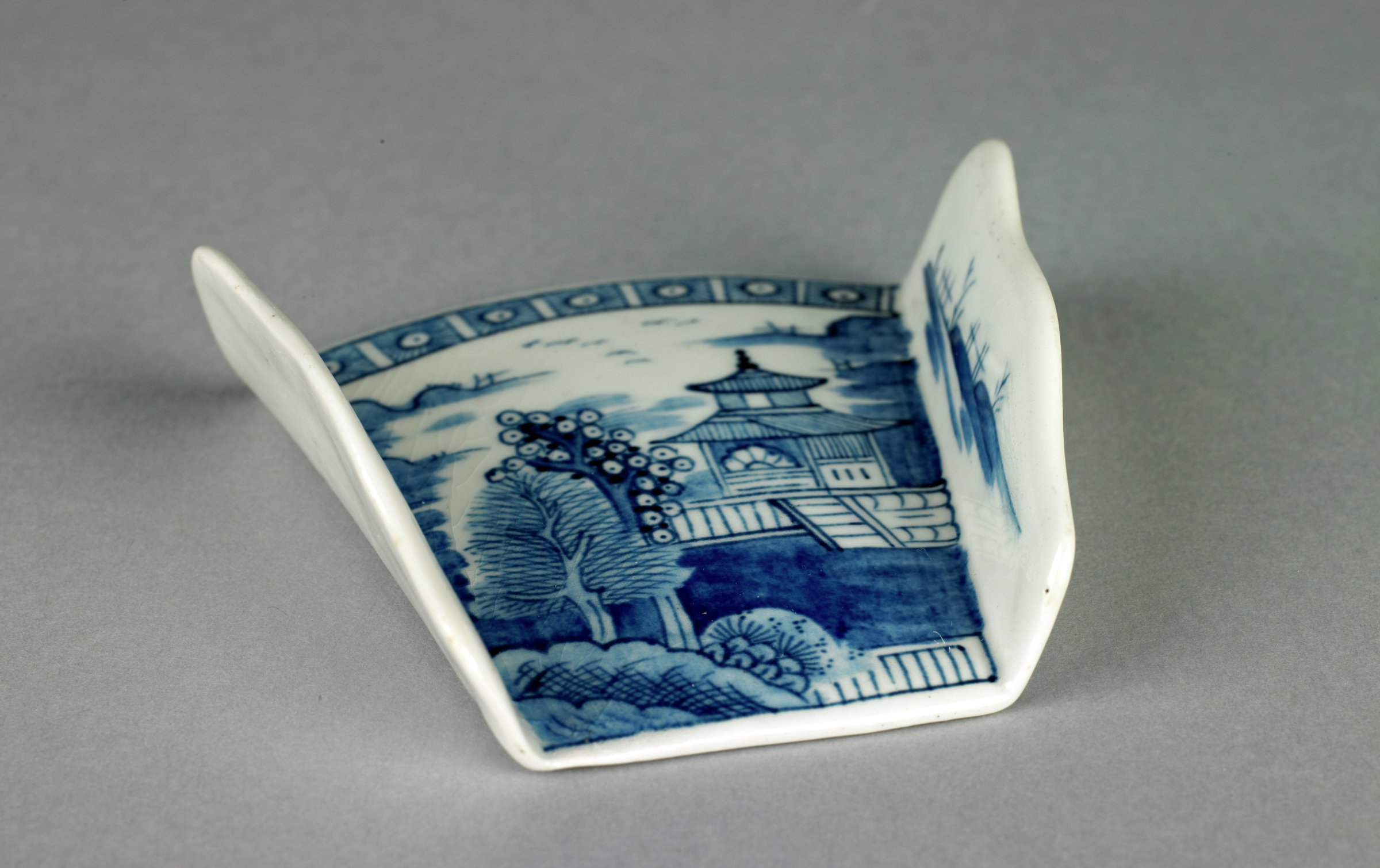 """Small asparagus shell, or server, of white soft-paste porcelain with low vertical, scalloped sides that taper towards one end, open at both ends to allow bundles of asparagus spears to be contained inside, the interior printed in underglaze blue in a variation of the Caughley """"Temple"""" pattern, the border above comprised of a series of blue squares with round reserves and blue dots."""