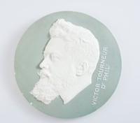 """Large, round portrait medallion of white jasper with green jasper dip and in white relief the portrait head left of Dr. Victor Tourneur (1878-1967), Belgian numismatic, historian, ethnologist, bibliographer and professor, and chief curator of the Royal Belgian Library from 1929-1943. He was a member of the Royal Academy of Belgium, the name """"Victor Tourneur Dr Phil:"""" running vertically on the right."""