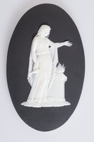 Oval black jasper plaque with white relief female figure at an altar meant to be a sacrificial scene, by Bert Bentley