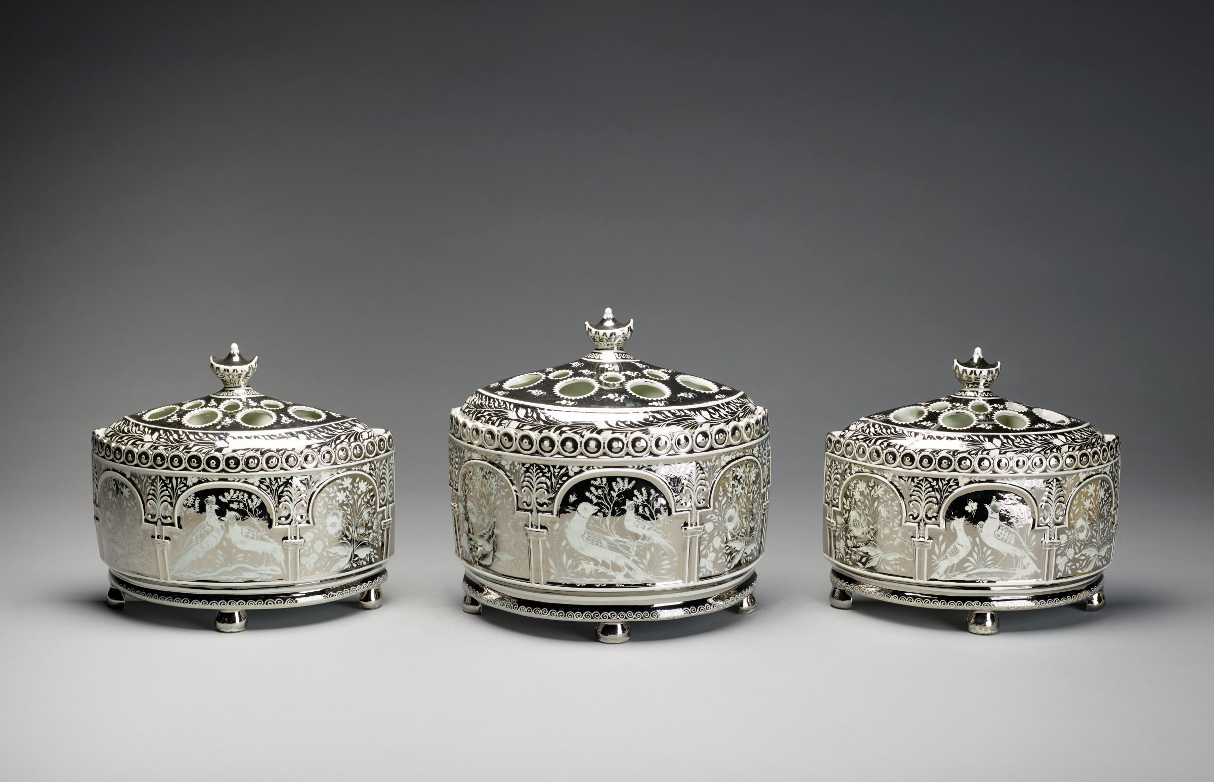 Three-piece bough-pot garniture of creamware covered with a pearl glaze, each of D-shape with convex fronts and flat backs, each resting on three ball feet, the bodies decorated only on the front with silver resist lustre in a pattern of three arches decorated with typical Leeds-style birds and foliage, with a border of repeating circles above, the covers pierced with both large and small holes, with urn-shaped finials.