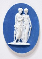 Oval cameo of white Jasper ware with blue dip and appled white bas-relief in imitation of a carved classical cameo. Two women standing slightly overlapped in classical robes, part of an existing larger composition of the three Graces. One stands against a two-legged bench or seat