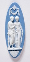 Elongated oval light blue jasper cameo with white relief of two women part of the three graces, Aphrodite and Athena below a floral swag