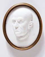 Oval white glass medallion with three-quarter portrait of a unidentified man, in metal mount