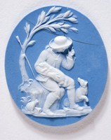 """Oval medallion of light blue jasper with white jasper relief depicting the """"Bourbonnais Shepherd,"""" a man sitting on a rock under a tree with a dog."""