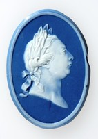 Oval dark blue jasper medallion with white relief profile portrait of King George III (1738-1820) facing right., cracked.He is shown in profile wearing a laurel wreath like a Roman Emperor. He was married to Queen Charlotte after whom Wedgwood's Queen's ware was so named in her honour.