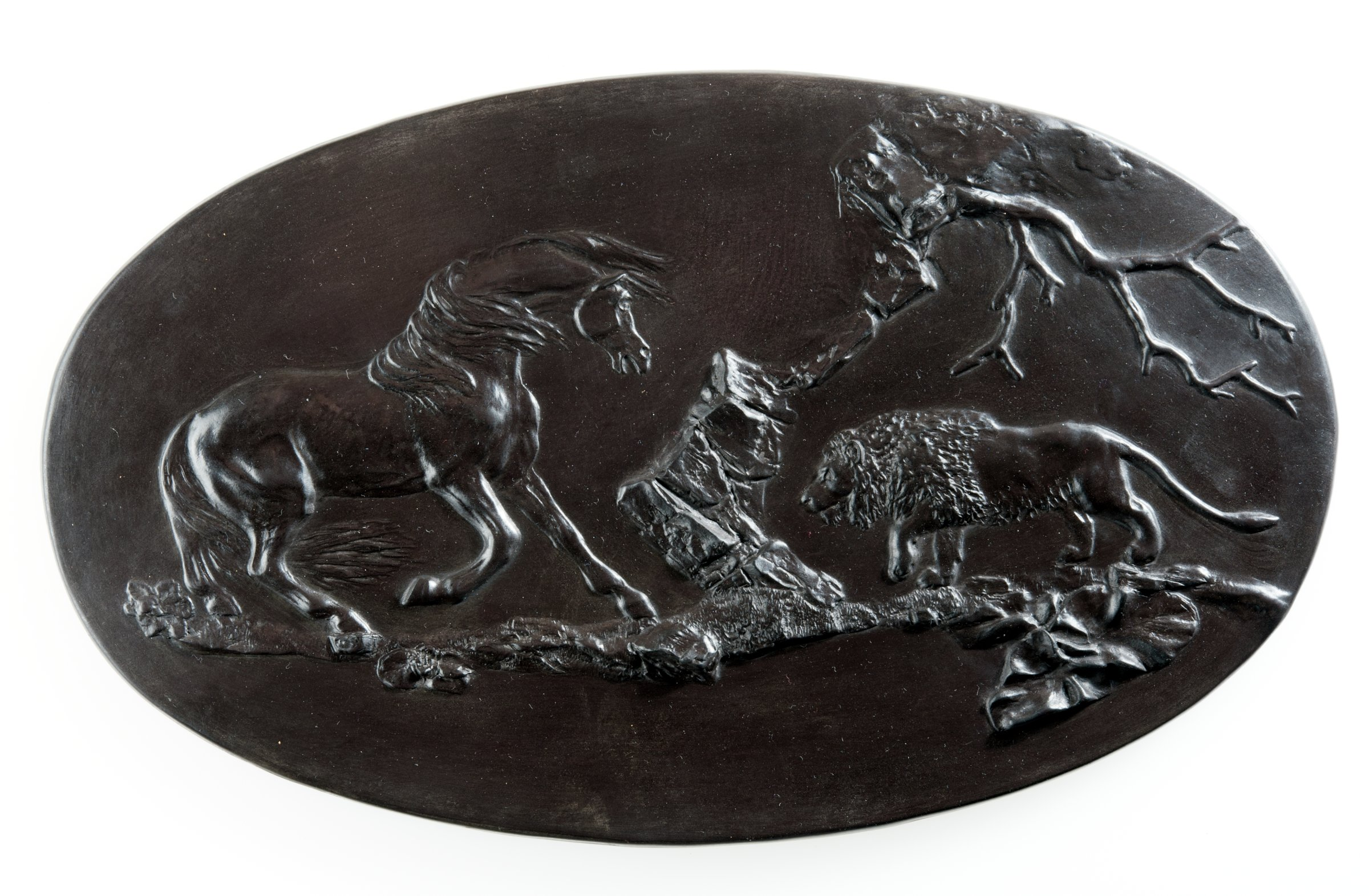 Large oval plaque of black basalt with with a scene of a horse frightened by a lion approaching from the right in a landscape.