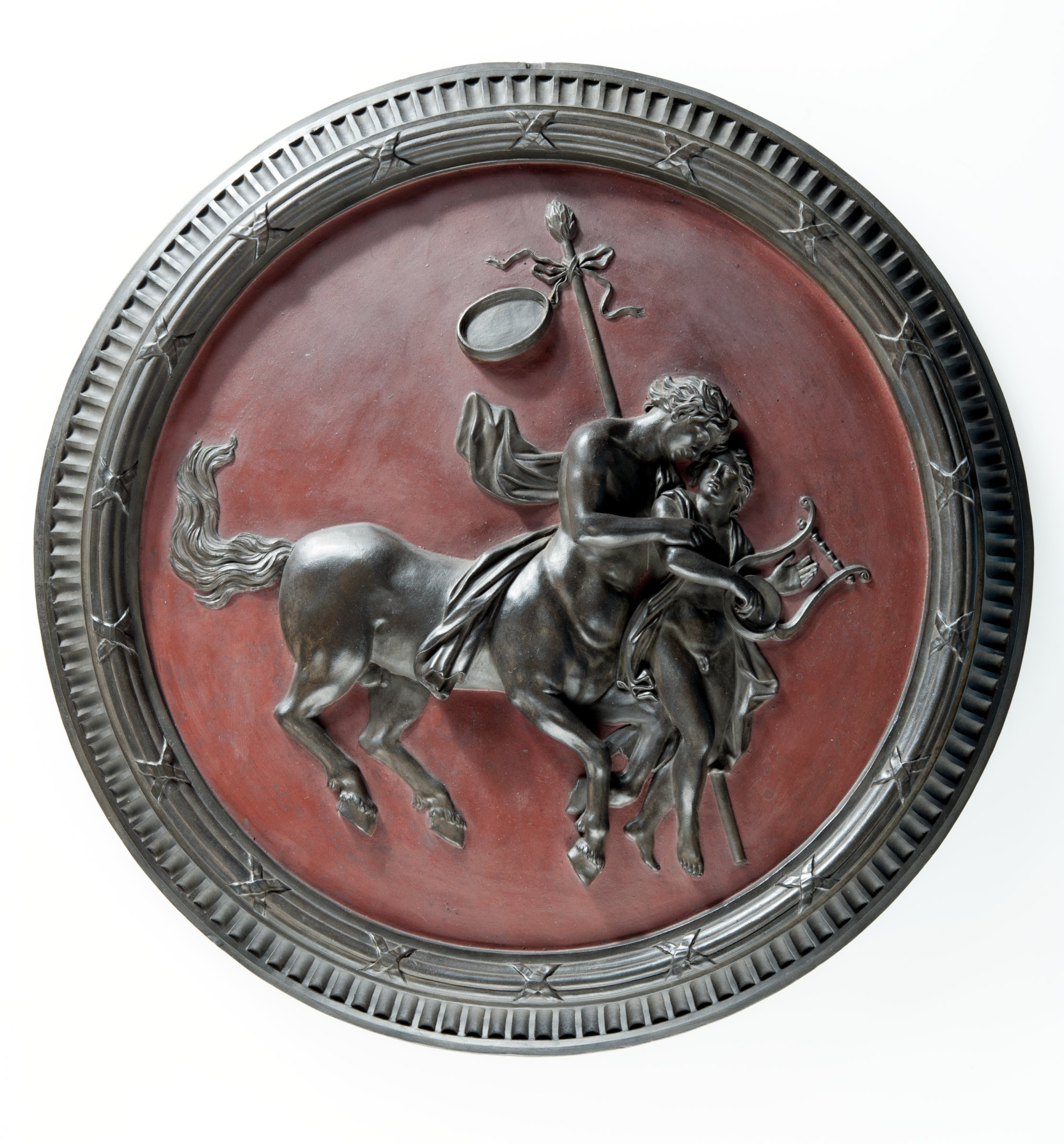 Large round, self-framed plaque of black basalt with the image of a Centaur teaching Achilles the kithara against a red encaustic ground.