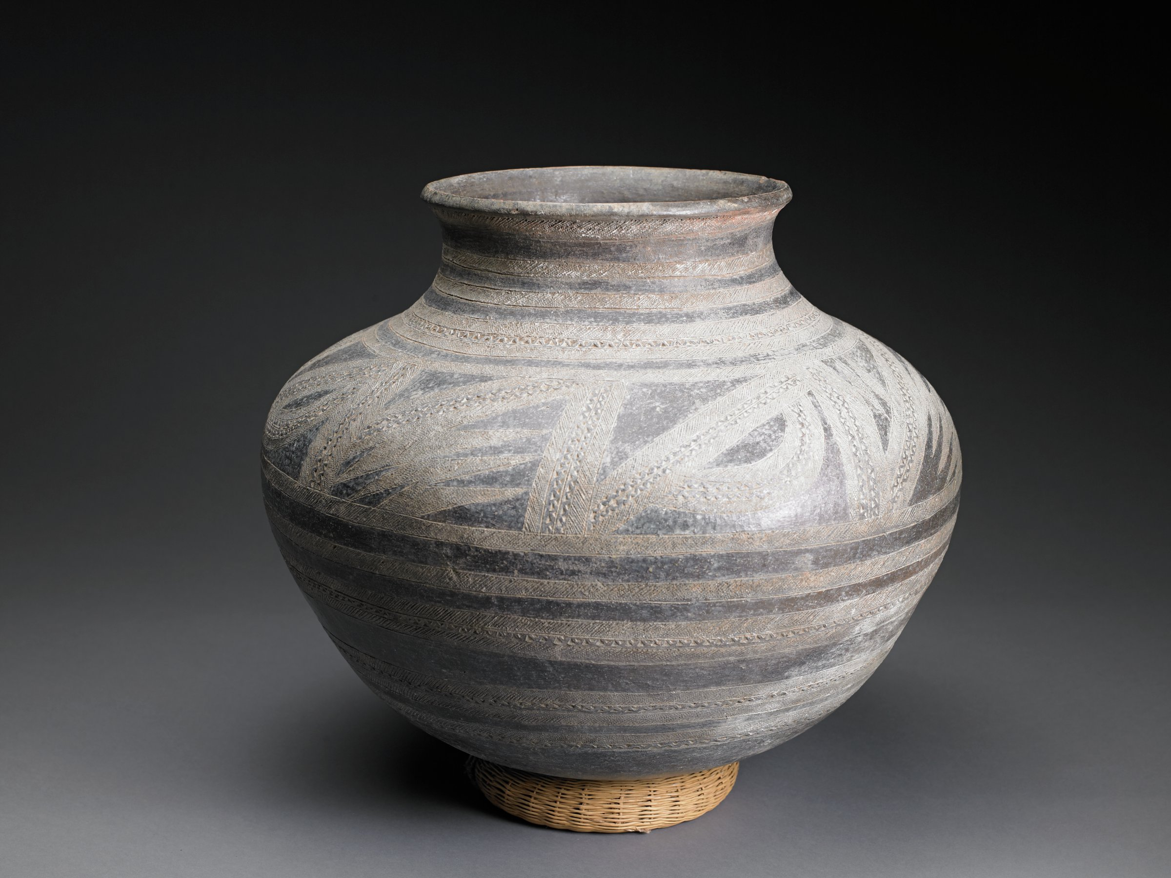 Wide vessel has narrow neck with flaring rim. Bands of incised patterns on neck and body of vessel; shoulder features free-form, ribbon-like patterns.