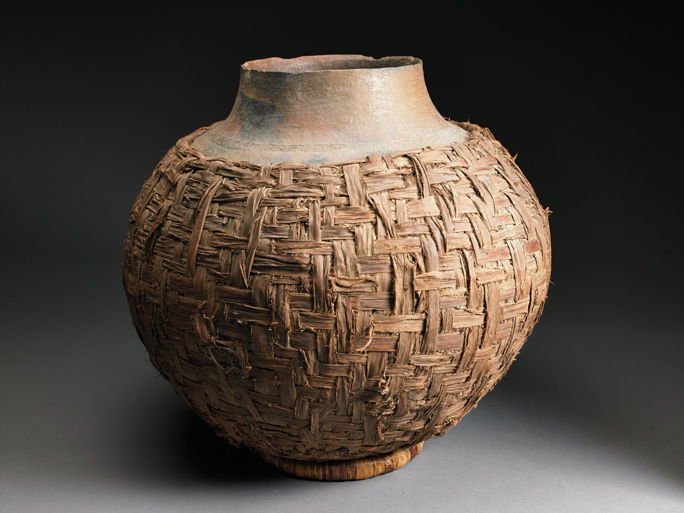 Globular vessel with narrow neck and mouth has woven basketry cover
