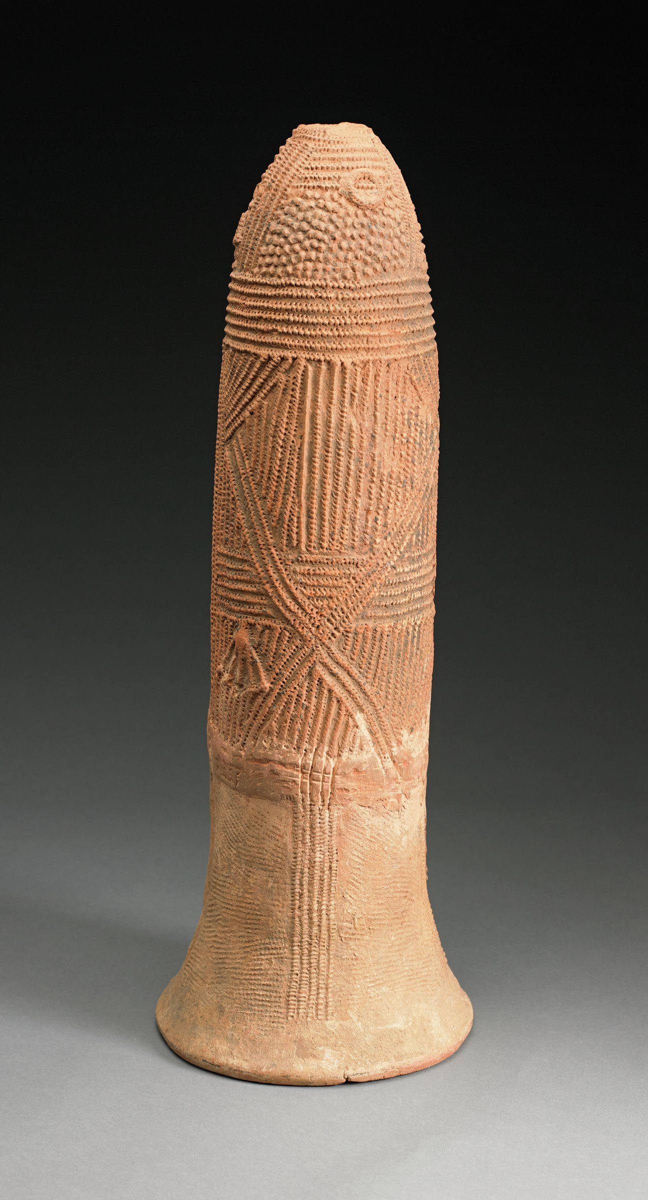 Phallic-shaped vessel with flared opening at the base, covered with patterns of reticulated ridges and raised bumps