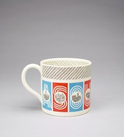 """Large creamware mug decorated with nine rectangular panels, each either red or blue and each with a letter in silhouette that together spell out the words """"A SOUVENIR"""", superimposed on each of the letters is a line-drawn vignette of London landmarks, including the Tower Bridge; Westminster Abbey; the Post Office Tower; the Tower; Trafalgar Square; St. James Park; Big Ben; Buckingham Palace; and St. Paul's, the upper part of the mug, both inside and out, decorated with sets of three hand-drawn parallel lines on a slant."""