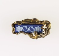 Rectangular dark blue jasper cameo with white relief floral decoration, set in gold plated metal as brooch