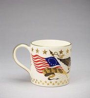 """Large creamware mug made to commemorate the American Bicentennial in 1976, the main body decorated at the top with a band of large gold stars and at the bottom with two bands of smaller stars, in the center are two American flags waving in the wind on either side of a black American eagle with outstretched wings highlighted in gold, on one side the """"Betsy Ross"""" flag with a gold banner below with the date 1776, and on the other a modern American flag with a banner and the date 1976, the loop handle and rim of the mug highlighted in gold."""