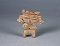 Standing female figure with oblong, oversized head, raised oval eyes, ear pendants and arms across waist