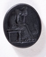 Oval black basalt intaglio with mourning seated female figure and peacock