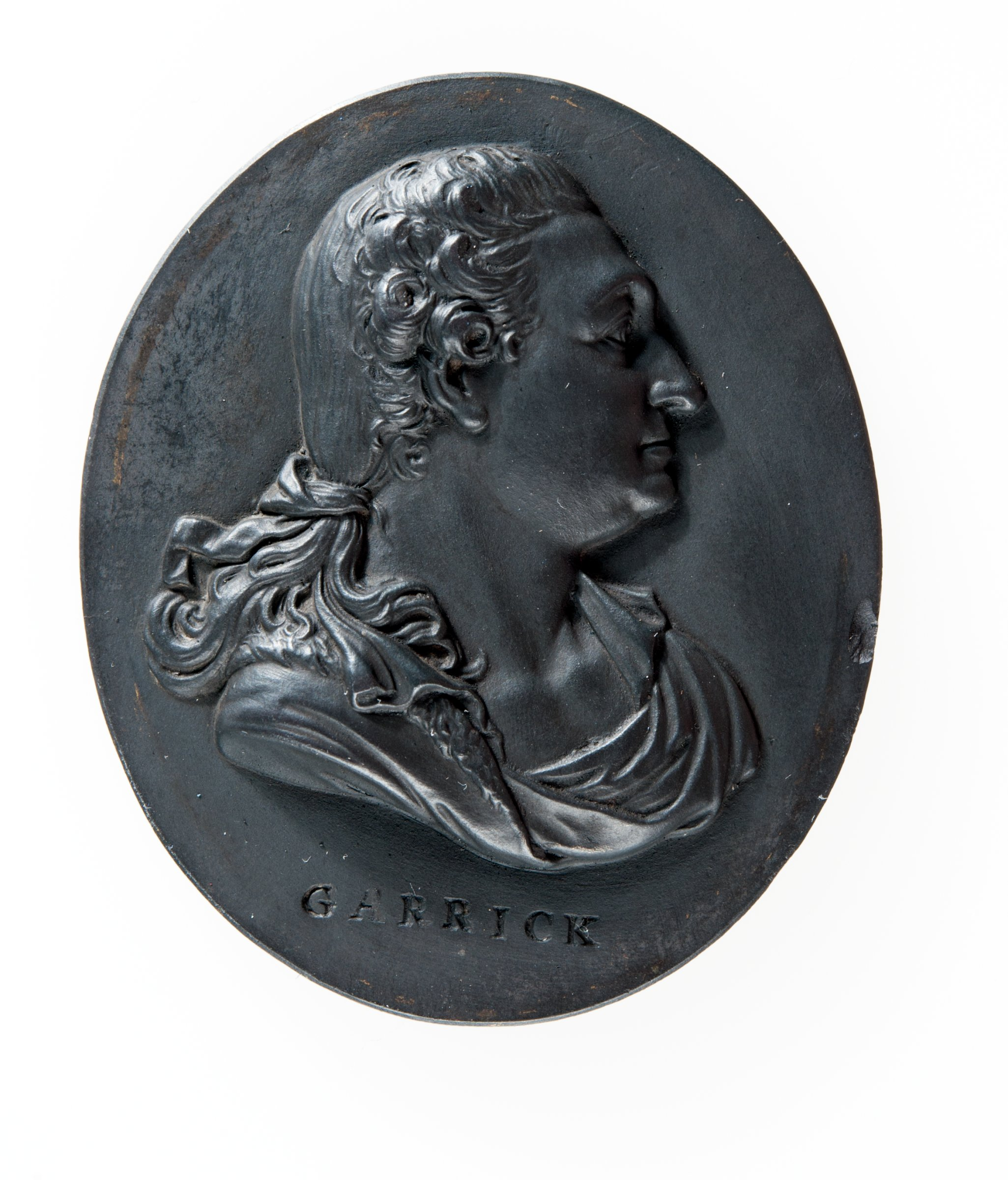Small oval medallion of black basalt with the relief profile portrait bust of David Garrick (1717-1779), English actor, in classical drapery, to right, with the name GARRICK below the truncation.