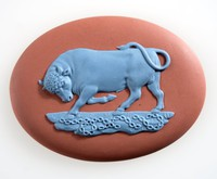 Oval terracotta jasper medallion with bright blue relief of prancing bull.