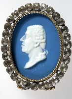 Oval dark blue jaser medallion with white relief portrait profile of Josef Franz Haydn (1732-1809) , set in plated silver frame surrounded with rhinestones. Haydn was a Austrian composer, he became a chorister in Vienna at the age of eight, and learned to play the pianoforte and the violin. When his voice broke he earned a scanty livelihood by playing the violin, and he had produced his first opera by the age of twenty. In 1758 he came to the notice of Prince Anton Esterhazy, and in the year following produced his first symphony. By this time he had achieved considerable popularity in Vienna, and Esterhazy made hi Vice-Kapellminster of the Court Orchestra in 1760. his success continued through Esterhazy's life and continued on after his death.