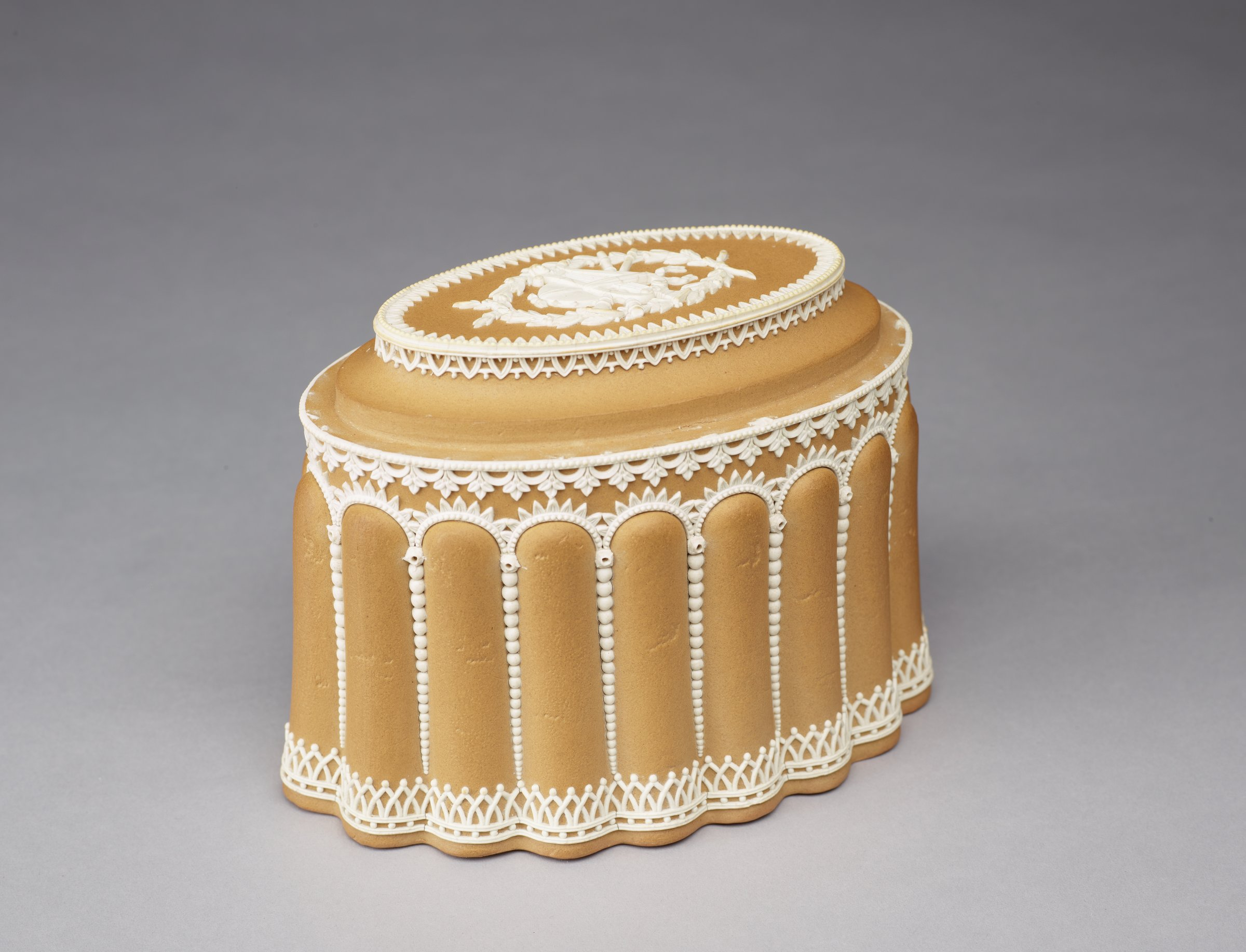 Pair of hollow, oval, caneware conceits in the form of iced cakes with white jasper applied elements to indicate the frosting, the sides in the form of lady fingers arranged vertically around the body and supporting a tiered top, the top layer decorated with a band of stiff leaf motifs and in the center an applied element comprised of musical instruments within a border of crossed laurel branches.