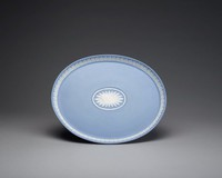 Oval tray of light blue jasper with light blue jasper dip, with raised edge decorated in white relief in a pattern of overlapping acanthus leaves and stiff leaf motifs, the center well with an oval reserve framed by a band of intertwined ribbons, in the center a sunflower, the white relief with some shading.