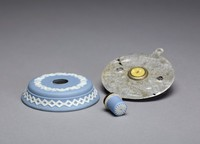 Large round doorbell of solid light blue jasper with white relief decoration, around the edge an intertwined zig zag band and on the top a band comprised of a leafy vine with a ribbon around it, the center button (loose) with a stylized floral element at the end, with a metal mount.