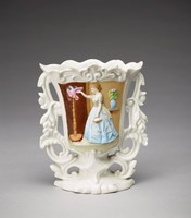 A mold-formed cottage-type vase with central cartouche featuring a polychrome domestic genre scene.  A woman in a grey top with white polka dots and blue skirt, standing at right, tends to a pink parrot with a blue head perched on a tall stand at left.  She extends her right arm, touching the bird's outstreched proper left wing. In her right hand, she holds a small basket containing something white, which she keeps to her side. To the woman's right, a table atop which sits a blue vase containing a pink flower.