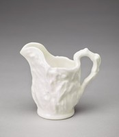 A small mold-formed pitcher decorated with corn stalks and ears throughout. The handle is shaped like a corn stalk. The corn design did not translate well to a small scale and is more difficult to read than with its larger counterpart.