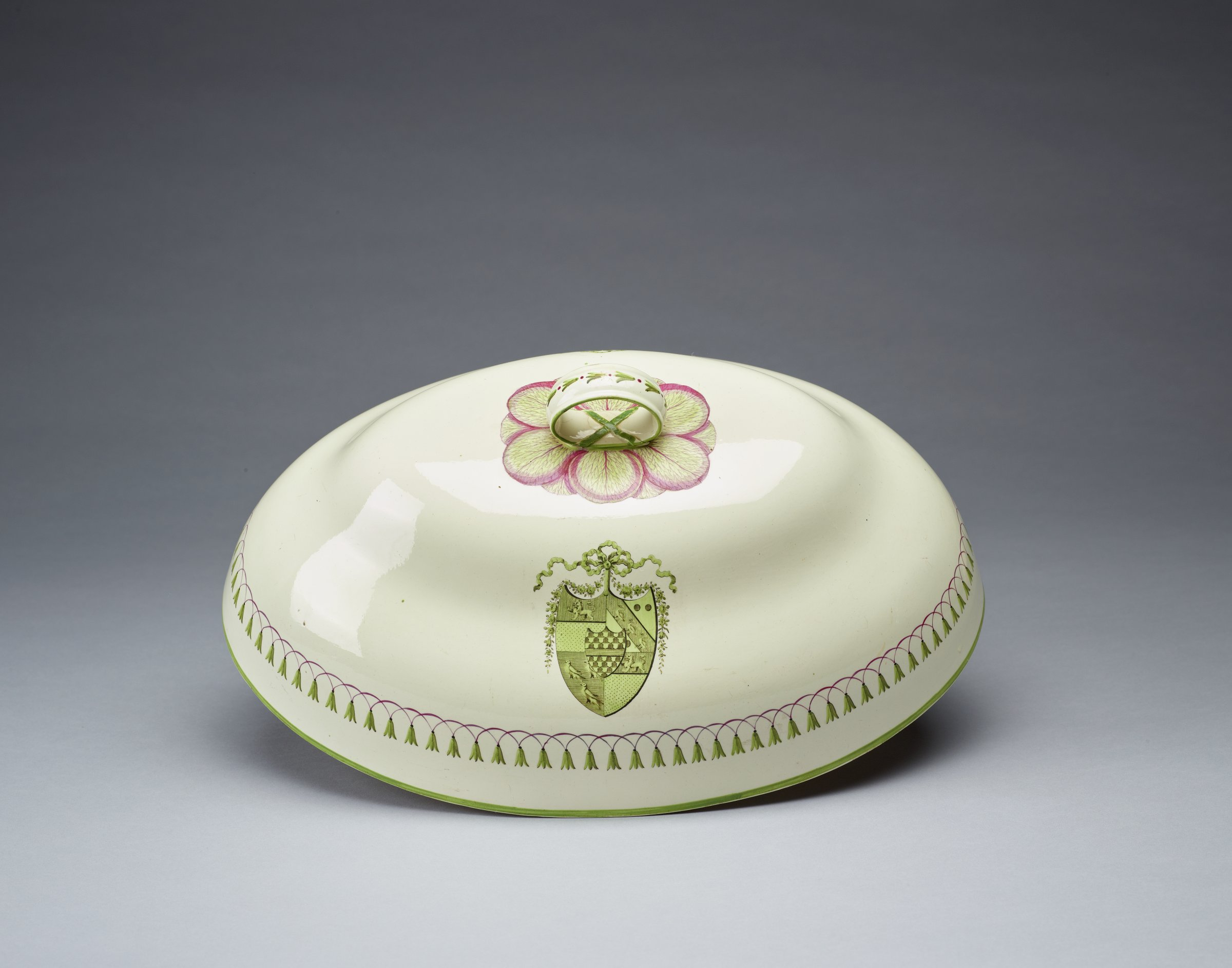 Large, oval, bell-shaped dish cover of creamware, painted in green enamel on both sides with the arms of Abney and Bracebridge (see notes) within a ribbon-tied garland, the lower rim is edged in green and the lower body has a band of dangling laurel leaves in green enamel suspended from pink stems, at the top a pattern of pink and green cabbage leaves surrounds the loop handle, which is edged in green and has a decorative X at the base.