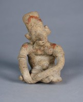 Small effigy of a seated sleeping woman, legs crossed and hands resting on legs, head tilted to one side, face heavy with prominent nose, touches of red pigment on hat and shoulder