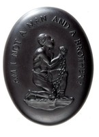 Small oval medallion of black basalt with in relief the image of an African slave wearing only a loin cloth, kneeling and in shackles, with his hands grasped together, around him the inscription AM I NOT A MAN AND A BROTHER?