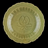 Small dish with barbed rim, row of carved lotus petals, lotus flower at center, brown wash on outer edge of base.