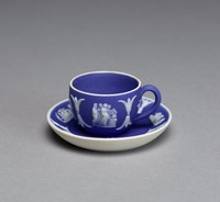Miniature cup and saucer of white jasper with dark blue jasper dip and white relief decoration, on both cup and saucer tiny relief scenes including on the cup Aurora, classical figures, and classical figures at an altar, on the saucer Romulus/Remus with a wolf, Venus and Cupid, Cupids riding a sea monster, Cupids with an urn, and Cupid riding a sea monster.