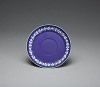 Saucer of white jasper with dark blue jasper dip and white relief decoration around the inner rim in a pattern of leafy vines, part of a service made for Capern's bird seed merchants in Bristol.