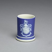 """Miniature commemorative spill vase of cylindrical shape of white jasper with dark blue jasper dip and white relief decoration, on one side the portrait bust of Josiah Wedgwood with the name JOSIAH WEDGWOOD and dates 1730-1795 in banners below, on the other the coat of arms of the Wedgwood baronetcy Gules four Mullets in Cross and a Canton Argent and on a Ducal Coronet a Lion passant Argent with the motto """"Obstantia Discindo"""" (I split asunder obstacles) in a banner below."""