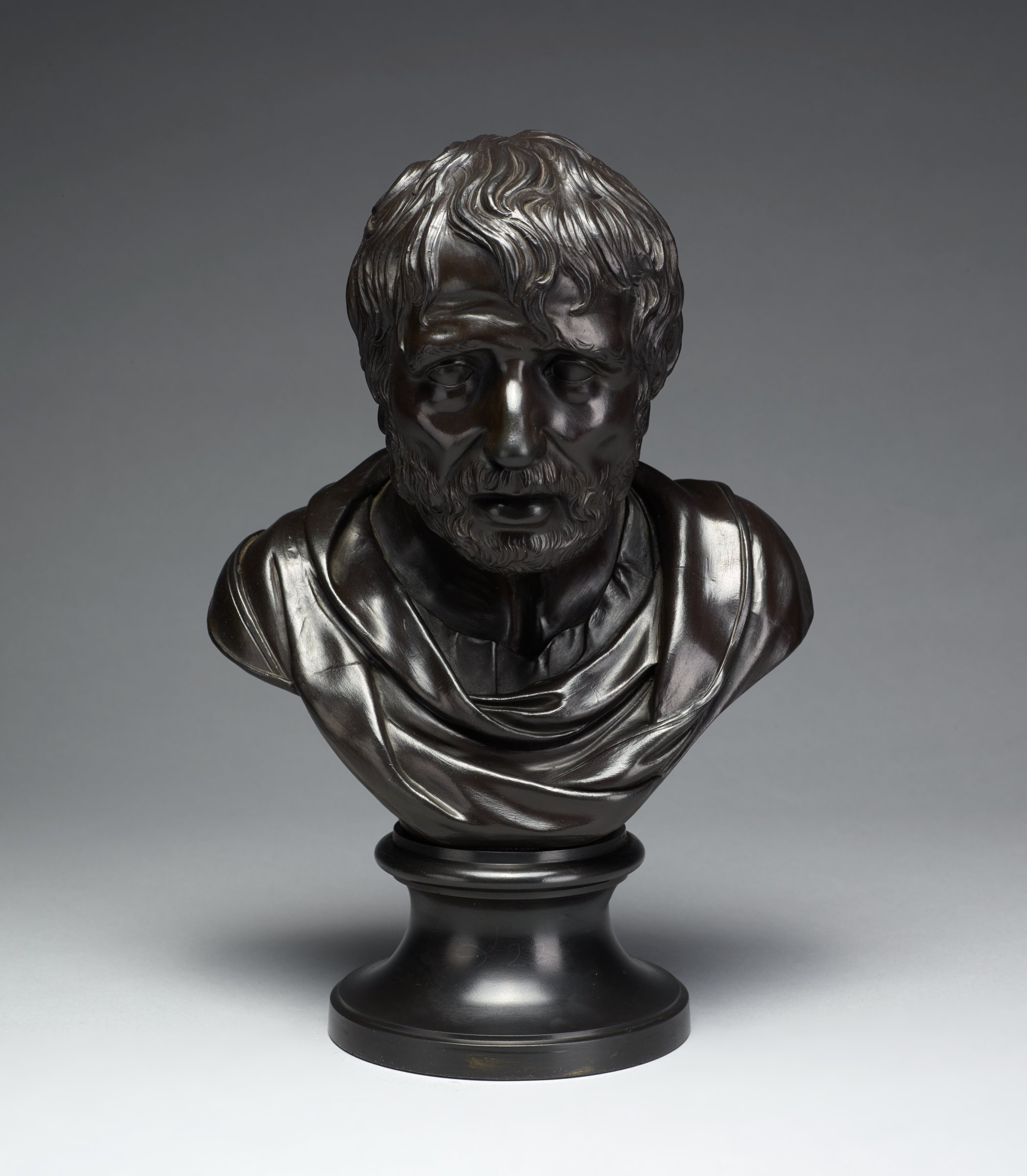 Portrait bust in black basalt of the Roman poet Seneca on round socle, the poet in classical drapery.