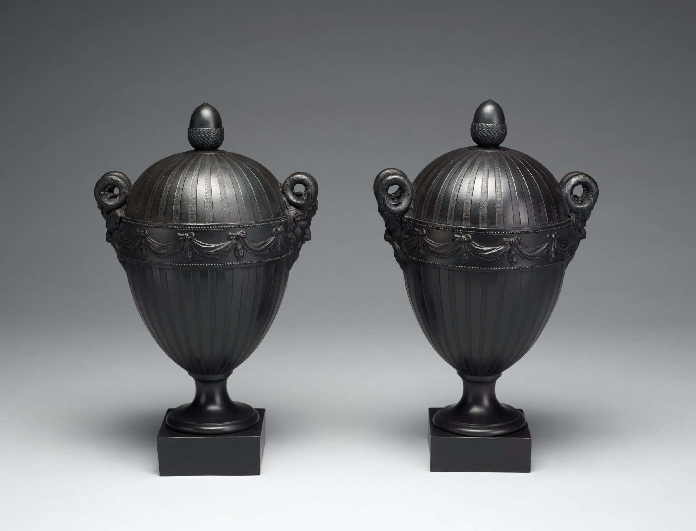 Pair of purely decorative vases of black basalt, each of urn shape and resting on small round foot mounted on a small square plinth, the body engine turned in a vertical stripe pattern and with swags around the shoulder, the permanently attached cover domed and with an acorn finial, with two horned mask handles.