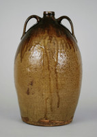 Large jar with strap handle on either side of shoulder, brown with darker brown drippy glaze on lip and shoulder and dripping down into body, double dipped