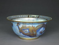 Dragon lustre bowl with wide lip, lavender/blue exterior and pale turquoise pearlized interior. A continuous pierced golden band pattern is set at the upper and lower rim of the bowl. Two outstretched four-legged, four-clawed golden dragons with scales and curled tail stretching across nearly half of the bowl, each. The dragons have a fierce look with bulging eyes, two horns, a mane and spikes along their backs. The spikes, part of the face, horns and claws are highlighted with red glaze. The wide lip is decorated with a golden geometric pattern over a blue glaze. A golden husks of wheat design is arranged below. Three framed medallions depicting different Asian-inspired architecture and vegetation intersecting the band design. The bottom and the lower half of the bowl are decorated with a large intertwined four-legged, four-clawed golden dragon, which is not well defined. The outline of the dragon is done in gold over a wash of blue glaze with some red highlights.