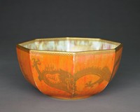 Octagonal dragon lustre bowl with vibrant orange exterior and pale turquoise and ocher interior. The upper and lower rim of the bowl is decorated with a golden, pierced band pattern and a sold golden trim on the upper rim. Two outstretched four-legged, four-clawed golden dragons with scales and curled tail stretching across three fields of the octagonal bowl, each. The dragons have a fierce look with bulging eyes, two horns, a mane and spikes along their backs. There are two simple, golden, swirl patterns on opposite sides of the bowl, dividing the dragons.The same golden, pierced band pattern, two dragons and swirl motifs are decorating the inside of the bowl. The bottom is highly decorated with golden geometric and floral patterns.