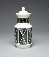 Creamware apothecary jar of baluster shape, the main body and neck silkscreened with a pattern of triangles, or diamonds, against a striated, striped ground, colored in shades of blue, yellow and black, the domed cover with ball finial.