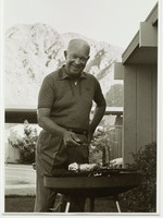 President Eisenhower cooks at an outdoor grill with mountains in the distance.