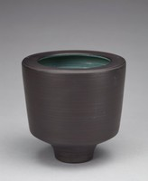 Vase with a cylindrical form and tapered base. The exterior is decorated with interspersed dimensional bands. The interior is glazed a gray-blue inconsistently, with black specks throughout. The lip of the vase extends towards the vase's center, parallel to the base.