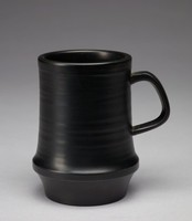 Mug with a cylindrical form thta flares at the form's bottom and tapers towards the base. The exterior features plain, dimensional bands most likely formed from the shaping process. These bands do not continue past the flared part of the mug and the bottom part past it is smooth. The cup's handle is a rounded square, placed at an angle to the cup. The cup's interior is also uniformly glazed.