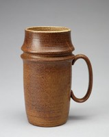 Mug with a rounded cylindrical form that flares out at two points and tapers towards the base. The mug's exterior is speckled dark brown stoneware. Two areas near the handle appear almost smeared, like they were disturbed before the glaze was dry. The exterior of the mug has thin horizontal, imprinted lines uniformly circling the form. The mug has a rougher texture nearer to the lip and there are visible air bubbles on the body. The lip and interior are off-white toneware with dark-brown specks.